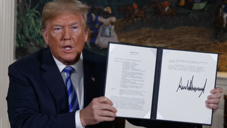 President Donald Trump shows a signed memorandum to pull out of the Iran nuclear deal.