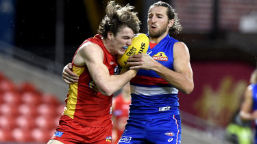 Charlie Ballars of the Suns faces a fierce attack from Bulldogs captain Marcus Bontempelli.