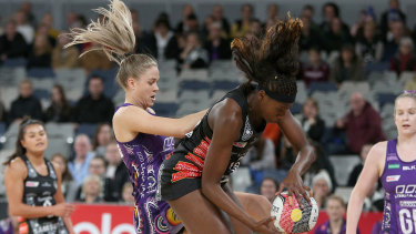 Feathers fly: Collingwood's Shimona Nelson  takes possession against Kim Jenner of the Firebirds.