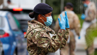 A member of the British armed forces directs a driver at a COVID-19 mobile testing centre in Leicester.