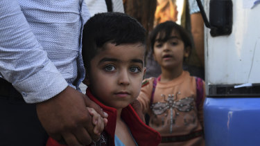 A Syrian boy holds his father's hand as he arrives at the Bardarash refugee camp.
