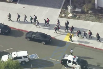 People are led out of Saugus High School in the city of Santa Clarita.