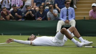 Kyrgios lays on the court after diving for a shot against Thompson.