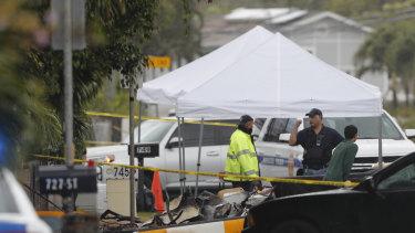 Investigators stand around the wreckage.