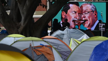 A billboard ad featuring Mark McGowan goes by 'tent city' in Fremantle as the camp is closed and homeless people are bussed to temporary hotel accommodation.