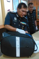 Director of Customs at Malaysia's international airport shows the bag allegedly containing drugs that was being carried by Maria Elvira Pinto Exposto when she was arrested.