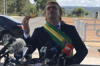 Comedian Marvio Lucio stands in front of members of the media while dressed as Brazilian President Jair Bolsonaro in Brasilia on Wednesday.