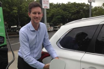 Main Roads Minister Mark Bailey charges an electric car in Cairns at the northern edge of Queensland's electric super highway.