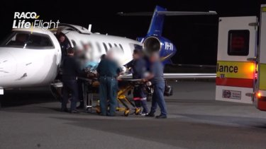 One of the injured miners lands at Brisbane Airport. All five suffered upper torso and airway burns.