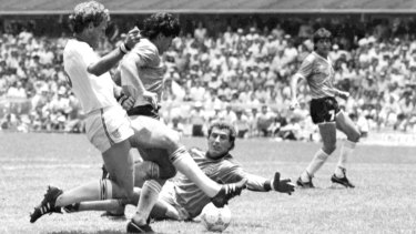 Diego Maradona (second left) is about to score his second goal against England. England's Terry Butcher (left) tries to tackle Maradona, while England's goalkeeper Peter Shilton is on the ground.