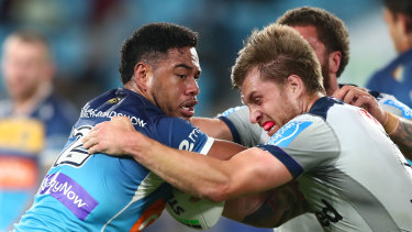 Greg Marzhew of the Titans tries to break free from Melbourne's Cameron Munster.
