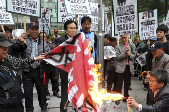 Protesters burn a Japanese rising sun flag in front of the Japanese embassy in Seoul, South Korea, in 2013.