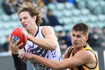 Nat Fyfe of the Dockers and Daniel Howe of the Hawks contest the ball.