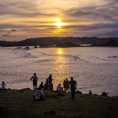 Tourists and locals gathering to watch the sunset on Bukit Merese Hill in Lombok's south.