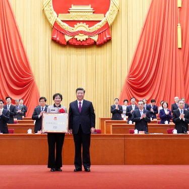 Xi Jinping presents an award to a village in Anhui province for being a role model in fighting poverty, in Beijing in February 2021.