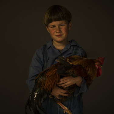 Caleb, 7, with a rooster.