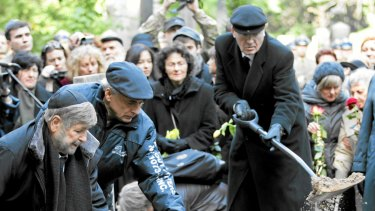 Paula Sawicka (centre, holding daffodils) watches as Marek Edelman is laid to rest.