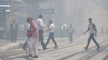 Pedestrians cross a hazy George Street as smoke haze blankets Sydney on Tuesday.