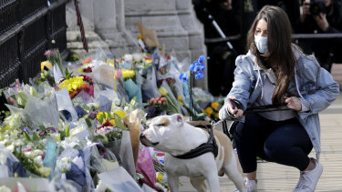 A mourner's dog smells flowers laid outside the gates of Buckingham Palace.
