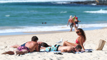 People relax at Burleigh Heads beach on the Gold Coast on Saturday after COVID-19 restrictions eased at midnight.