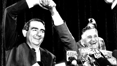 Mike Ahern and his deputy Bill Gunn give a victory salute in Mr Ahern's first press conference as premier.