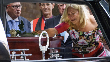 Kerri-Anne Kennerley places her hand on the casket following the funeral for her husband John Kennerley.