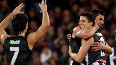 Trent Bianco celebrates a goal with Collingwood team mates Josh Daicos and Scott Pendlebury during the clash with the Crows at the Adelaide Oval.