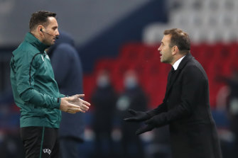 Basaksehir's manager Okan Buruk (right) reacts to fourth referee Sebastian Coltescu.