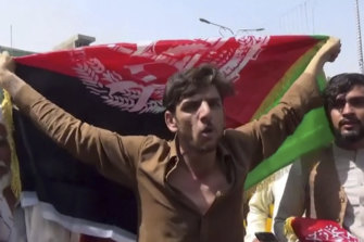 A man holds the Afghan flag during a protest in Jalalabad on Wednesday.