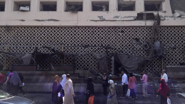 People survey the aftermath of a fiery car crash outside the National Cancer Institute in Cairo.