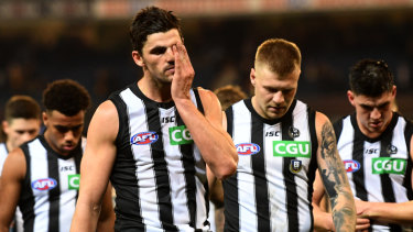 Scott Pendlebury and Jordan de Goey lead the Magpies off after a tough match against the Hawks.