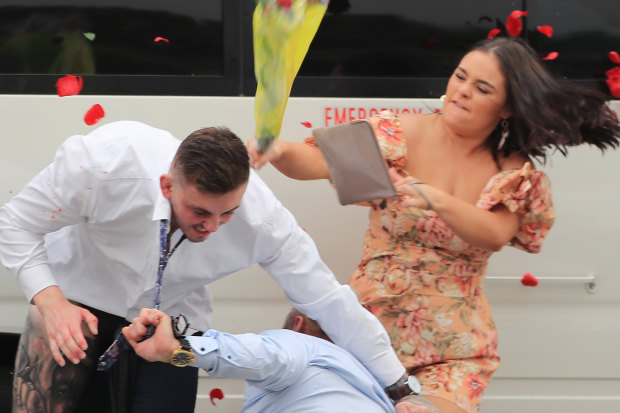 Blooming disgrace: A woman whacks two brawlers with a bunch of roses.