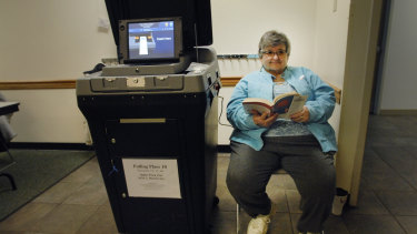 Election judge Carylon Richards reads a book as she waits for voters at the Miller Park Zoo during the Illinois primary on Tuesday.