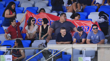 Deregistered player agent Isaac Moses (bottom right, in blue shirt and black cap) sitting with the Suaalii family on Saturday.