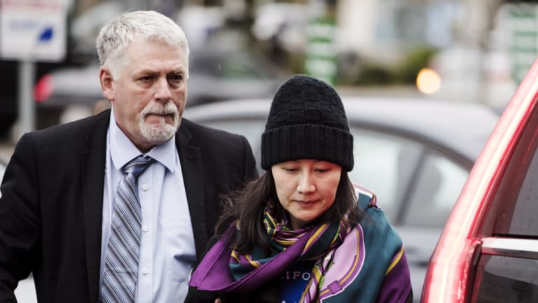 Huawei chief financial officer Meng Wanzhou arrives at a parole office with a security guard in Vancouver.