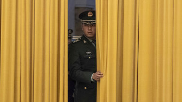 A member of Chinese People's Liberation Army waits for a welcome ceremony to start.