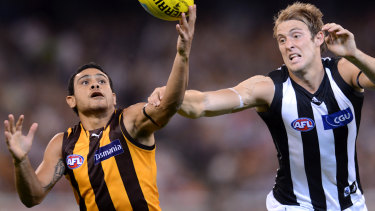 Hawk Cyril Rioli and Magpie Ben Reid battle for possession in 2012.