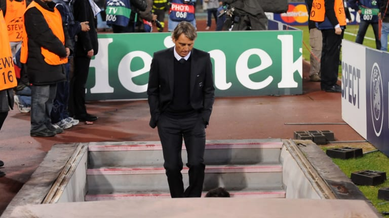 Scrutiny: Roberto Mancini leaves the field after a Champions League match back in 2011.