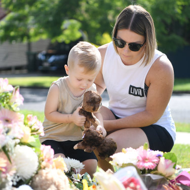 Chantel Taylor and her two year-old son Henley pause after placing teddybears at a makeshift shrine near the scene of the murders.