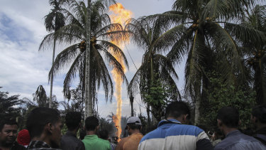 Curious onlookers watch as an oil well burns after it caught fire in eastern Aceh, Indonesia.