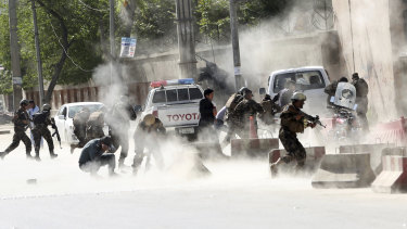 Security forces run from the site of a suicide attack after the second bombing in Kabul.