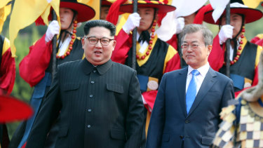 North Korean leader Kim Jong-un, left, and South Korean President Moon Jae-in walk together through a honour guard at the border village of Panmunjom in the Demilitarized Zone.