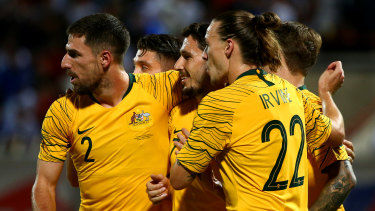 Matthew Leckie of Australia, centre, celebrates with teammates after scoring the Socceroos' opening goal against Kuwait.