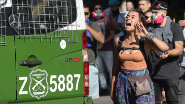A demonstrator shouts slogans near a police vehicle near Costanera shopping mall in the business district of Santiago on Wednesday.