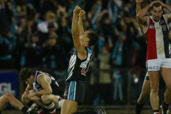 Port Adelaide's Warren Tredrea celebrates as St. Kilda's Stephen Powell and Robert Harvey are devastated.