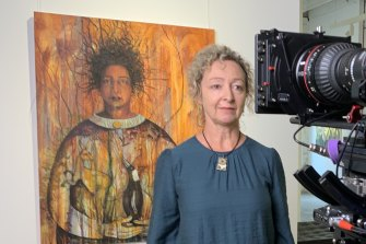 Artist Penny Lovelock, in front of one of her paintings, Out of the ashes, while filming We are Conjola.