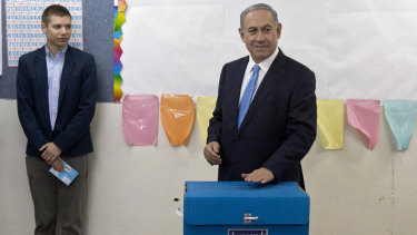 Israeli Prime Minister Benjamin Netanyahu, right, votes in Jerusalem in 2015, as his son Yair watches. Yair is no stranger to controversy, having been accused of living it up at taxpayers' expense.