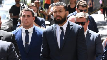 NRL players Adam Elliott and Asipeli Fine leave the Downing Centre Court on Monday.