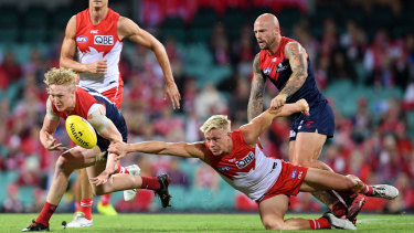 Contest: Melbourne's Clayton Oliver tussles with Swan Isaac Heeney.