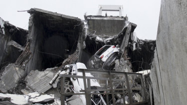 Cars are seen among the rubble of the collapsed bridge.